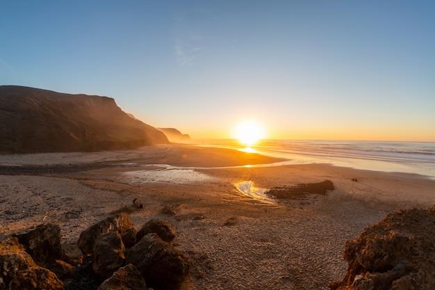 Paesaggio di una riva circondata da montagne e mare sotto un cielo blu durante il tramonto Foto Gratuite
