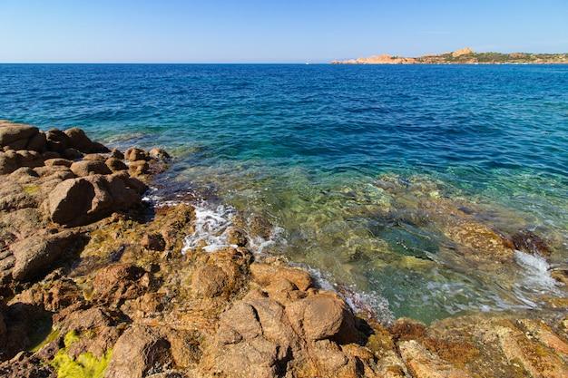 Colpo di paesaggio di grandi rocce, verdi colline in un oceano blu con un cielo blu chiaro Foto Gratuite