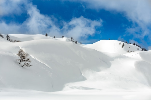 Landscape shot of hills covered with snow in a cloudy blue sky Free Photo