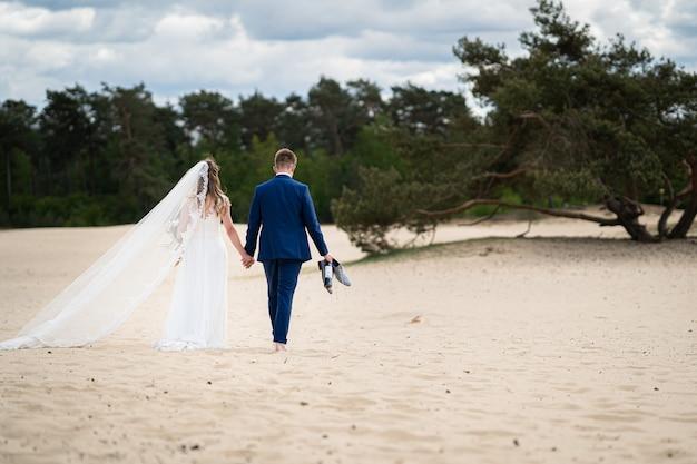 Пейзажный снимок пары, идущей по песку в день свадьбы Бесплатные Фотографии