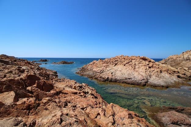 澄んだ青い空に大きな岩のある海岸の風景ショット 無料写真