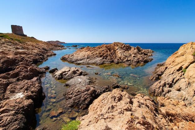 澄んだ青い空と青い海の大きな岩の風景ショット 無料写真
