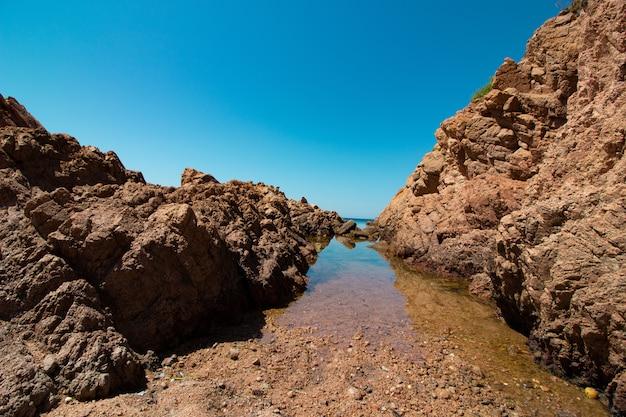 澄んだ晴れた青い空と外洋の大きな岩の風景ショット 無料写真