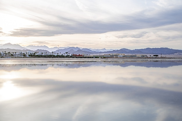 The landscape sky is reflected in the sea. city coastline with mountains on the horizon. Free Photo