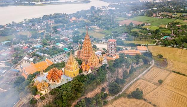 Landscape of wat tham suea, kanchanaburi thailand with smoke from burning rice stubble Premium Photo