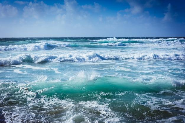 Paesaggio di un mare ondoso sotto la luce del sole e un cielo blu Foto Gratuite