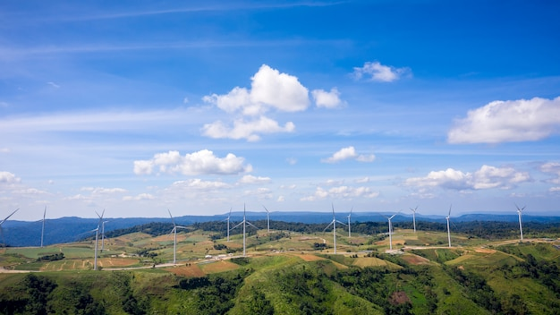 Landscape wind turbines on the mountain farmland and blue sky background Premium Photo