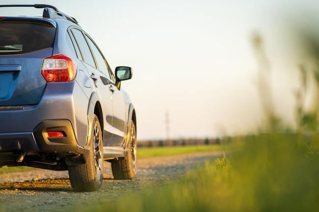 砂利道の青いオフロード車のある風景します。自動車での旅行、野生動物の冒険、遠征、またはsuv自動車での極端な旅行。日の出フィールドのオフロード4x4車。 Premium写真