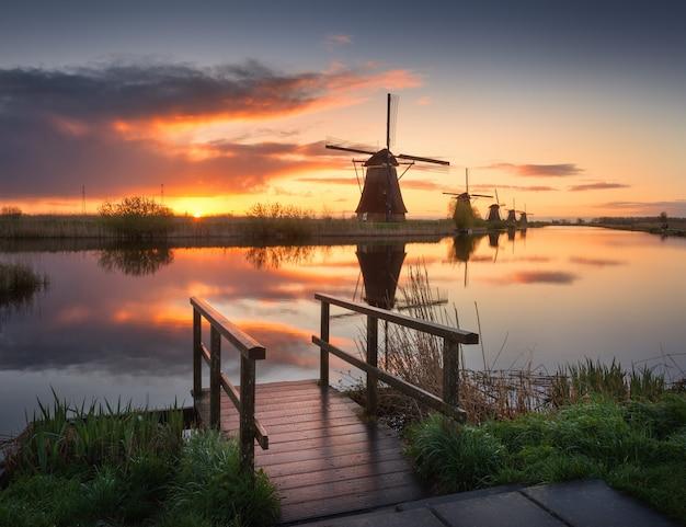 カラフルな日の出、美しい空で伝統的なオランダ風車のある風景 Premium写真