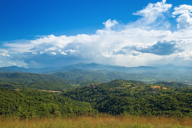 Langhe is a hilly area  in the province of cuneo in piedmont, northern italy. view of the valley after a storm. huge white clouds on a blue sky. Premium Photo