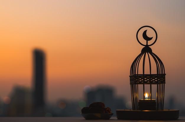 Lentera berlambang bulan di atasnya dan sepiring kecil buah kurma dengan langit senja dan latar kota untuk pesta muslim bulan suci ramadhan kareem.  Foto Premium