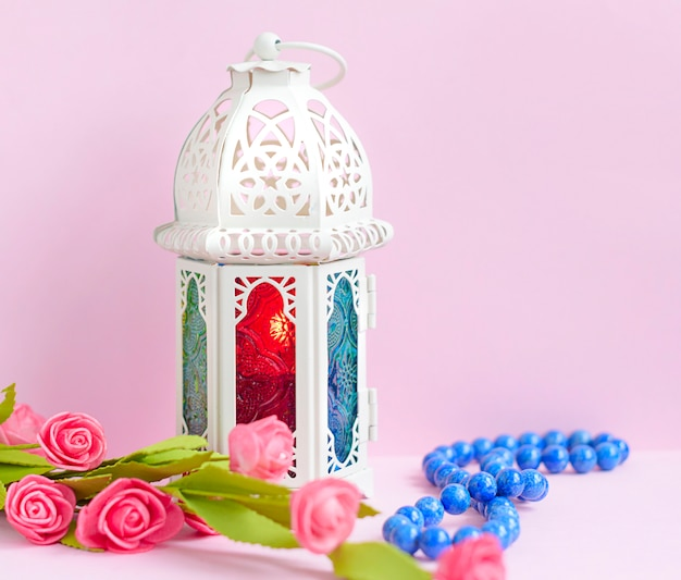 Lantern with candle and rosary beads Premium Photo