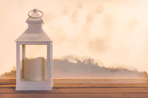 Lantern with candle on wood board near heap of snow through window Free Photo