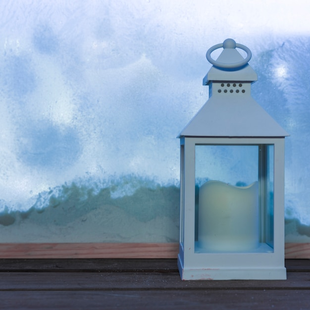 Lantern with candle on wood table near bank of snow through window Free Photo