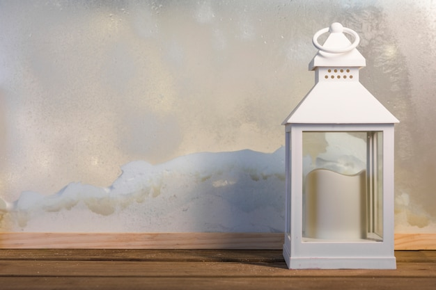 Lantern with candle on wooden board near heap of snow through window Free Photo