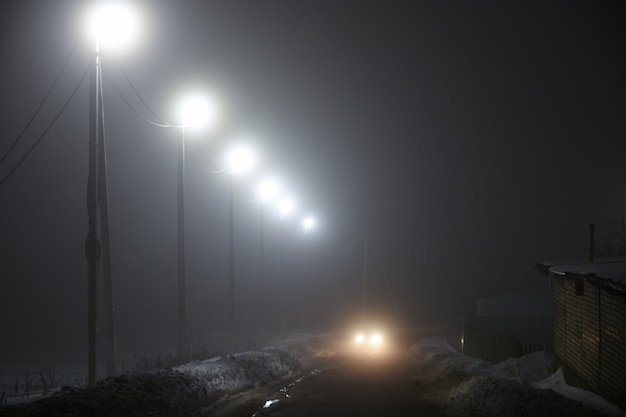 Lanterns along the night road in the fog Premium Photo