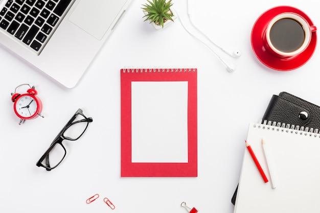 Laptop,alarm clock,eyeglasses,coffee cup,diary,earphones and laptop on white desk Free Photo