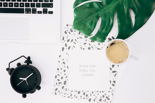 Laptop; alarm clock; monster leaf; coffee cup; adhesive notes with message and paper on white desk Free Photo