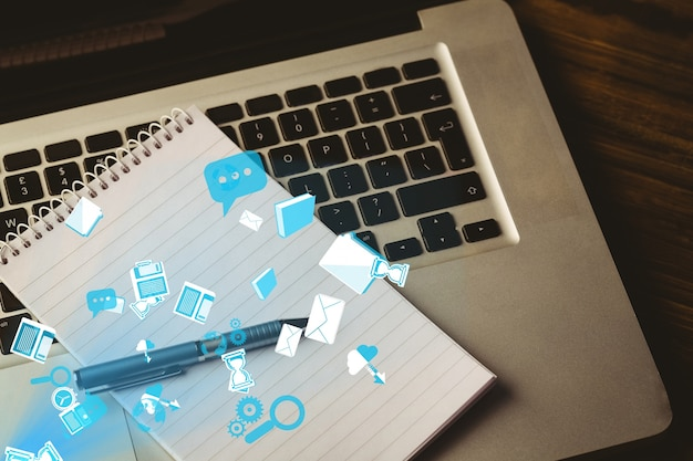 Laptop and notepad with app icons Free Photo