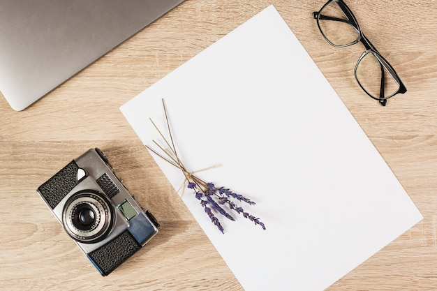 Laptop; camera; eyeglasses and blank paper with lavender twig on wooden table Free Photo