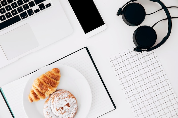 Laptop; cellphone; headphone; square grid paper; baked croissant and buns on diary over white background Free Photo