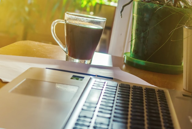 Laptop close up of a keyboard and a cup of hot coffee in the morning. selective focus. Premium Photo