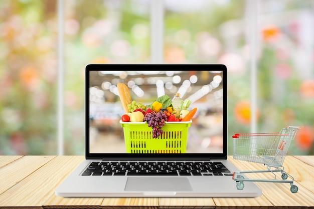Портативный компьютер и тележка для покупок на деревянном столе с окном и садовой абстрактной размытой концепцией продуктового онлайн Premium Фотографии