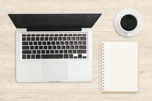 Laptop computer and blank notebook on wood table. top view business background. Premium Photo