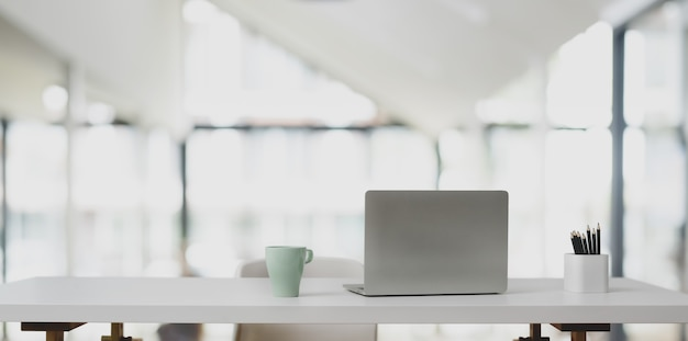 Laptop computer on white table and coffee cup in modern office Premium Photo