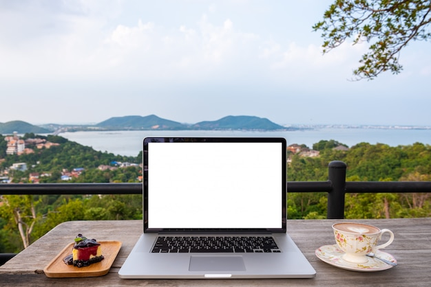 Laptop computer with strawberry cake and coffee cup on wooden table on the mountains city view