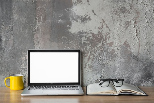 Laptop; cup; book and spectacles on wooden desk in front of old wall Free Photo