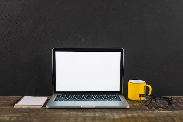 Laptop; cup; notepad and spectacles on wooden surface Free Photo