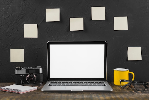 Laptop; cup; spectacles; spiral notepad and camera in front of adhesive notes stucked on blackboard Free Photo