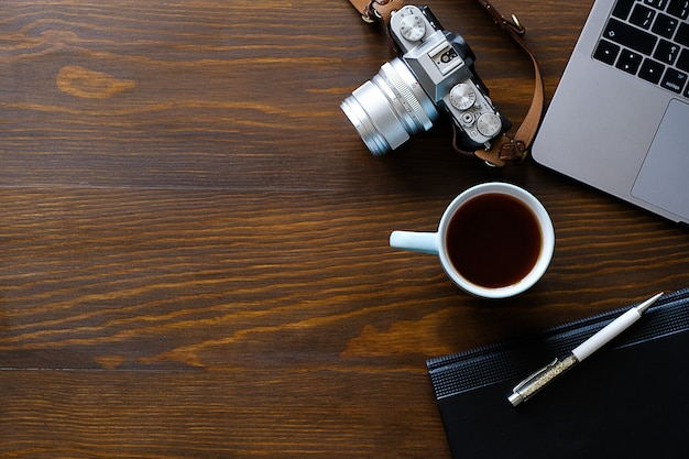 A laptop, a cup of tea, a camera and a notebook lie on a dark wooden table. the workplace of a photographer or a freelancer. copy paste for text. Premium Photo