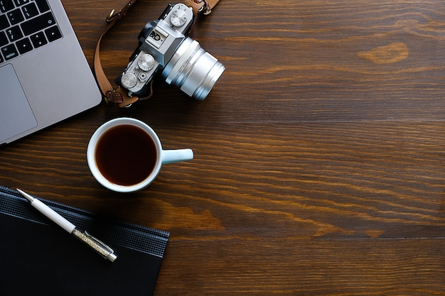 A laptop, a cup of tea, a camera and a notebook lie on a dark wooden table. Premium Photo