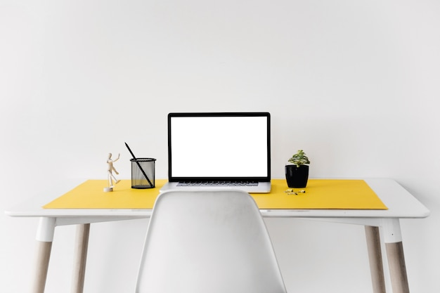 Laptop on desk against white wall Free Photo