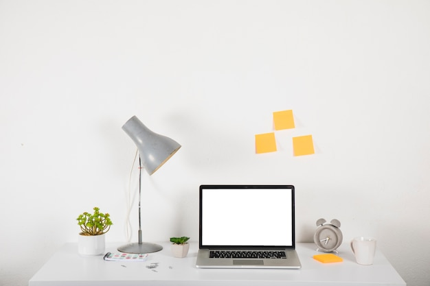 Laptop on desk near decorations and sticky notes Free Photo