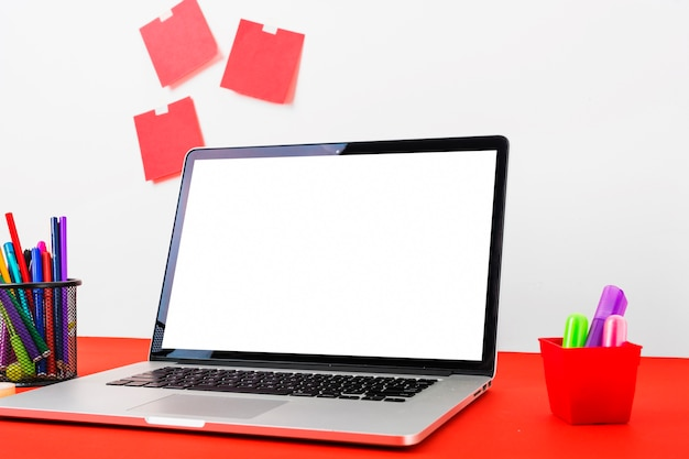 Laptop displaying white screen with colorful stationeries on red table Free Photo