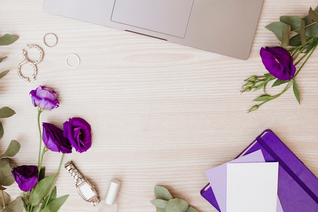 Laptop; earrings; wedding rings; wrist watch; nail polish; envelope; eustoma flowers and diary on wooden background Free Photo