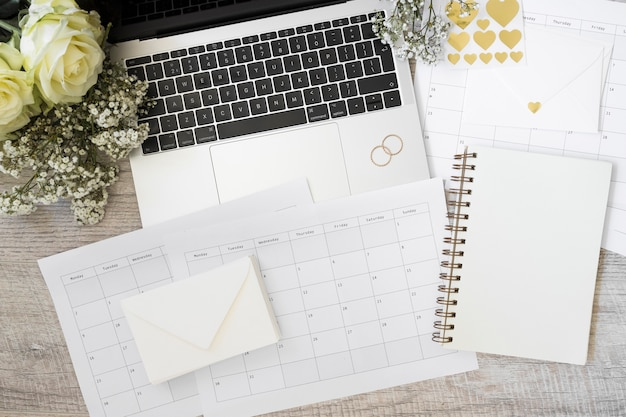 Laptop; flowers; envelope; calendar and spiral notebook on wooden desk Free Photo