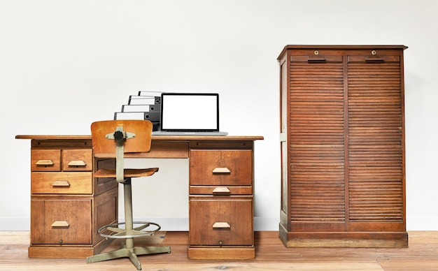 Laptop and folder lying on a vintage desk Premium Photo