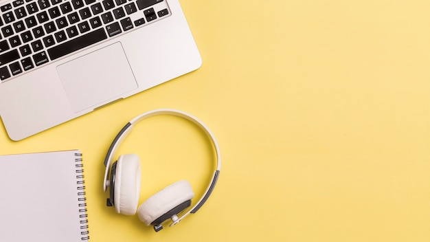 Laptop and headphones on yellow background Free Photo