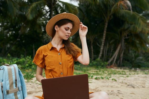 ラップトップ島の帽子と砂の上のバックパックで美しい女性 Premium写真