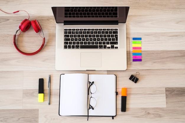 Laptop near eyeglasses, notepad and headphones on floor Free Photo