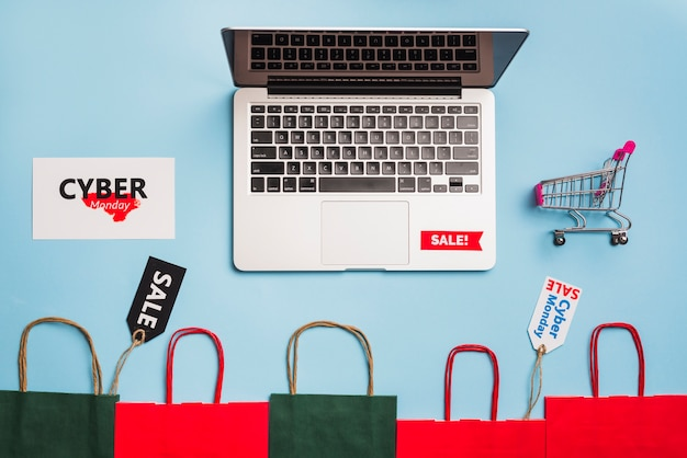 Laptop near tags, shopping trolley and packets Free Photo