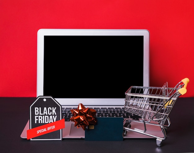 Laptop near toy sign, credit card and supermarket cart Free Photo