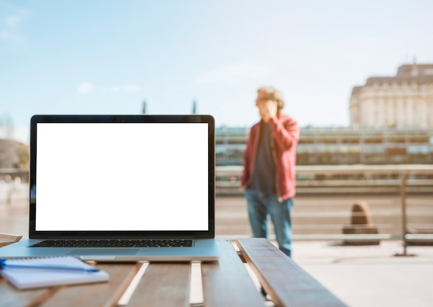 Laptop; notepad and pen on wooden table with man standing at background Free Photo