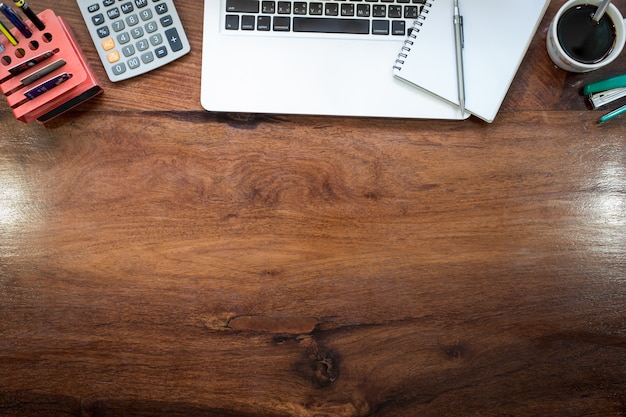 Laptop on Vintage Wooden desktop in modern office with accessories - top  view on desk from