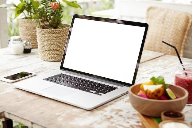 Laptop e altri dispositivi elettronici nell'area di lavoro. luogo di lavoro di affari con laptop moderno aperto e smart phone sulla tavola di legno. Foto Gratuite