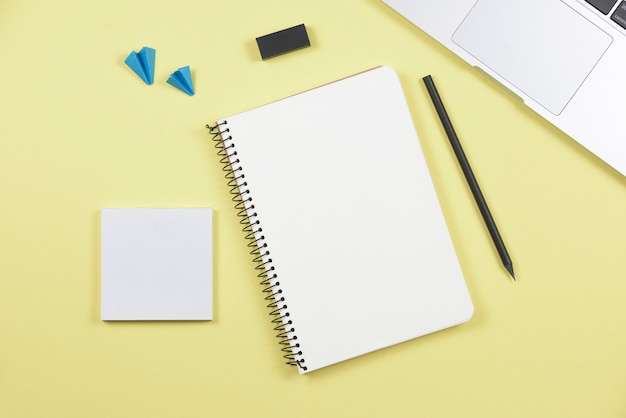 Laptop; pencil; spiral notebook; adhesive notepad; airplane and eraser on yellow background Free Photo